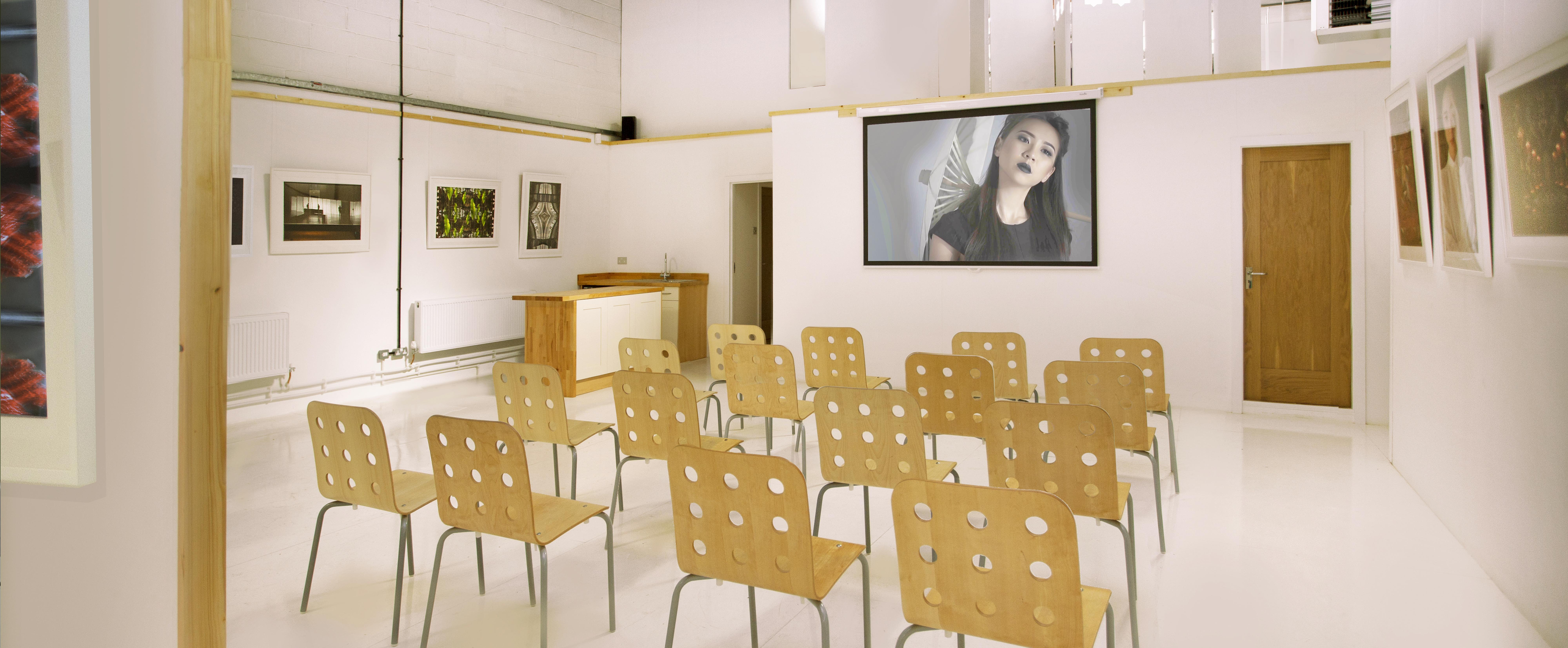 Rows of chairs facing a projector screen in the gallery